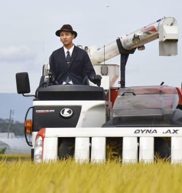 スーツ姿で稲刈りをする斎藤聖人さん=4日、山形県川西町