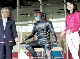 田口さん(右)と亀山紘石巻市長らが除幕し、披露された「仮面ライダーBLACK」のモニュメント