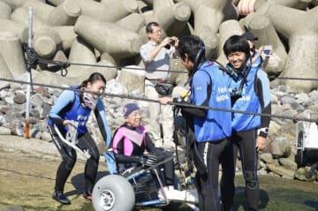 ボランティアのサポートを受けながら海辺に近づくダイバー(左から2人目)=小田原市江之浦