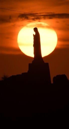 夕日に浮かぶマリア像=20日午後5時40分ごろ、天草市河浦町