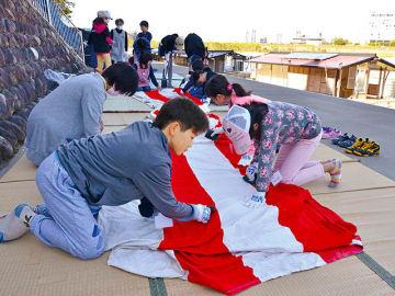 鵜飼観覧船の飾り幕をナイロンたわしでこする児童ら=岐阜市湊町、鵜飼観覧船乗り場