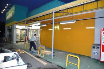 乗用車が店内に突っ込んだスーパー「おどや船形店」。破損したガラス部分は木の板で覆われている=15日、館山市船形