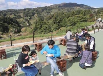 完成したおらたるの中庭で、山古志の特産品を使った食事を楽しむ人たち=21日、長岡市山古志竹沢