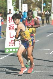 男子第3中継場で仙台育英の4区吉居(手前)が3区ムセンビからたすきを受け取って走りだす