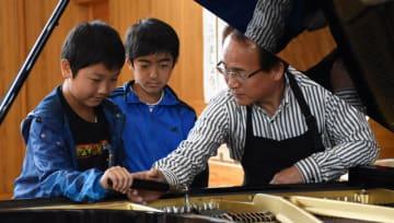山内さん(右)に教えてもらいながら、ピアノの調律をする児童