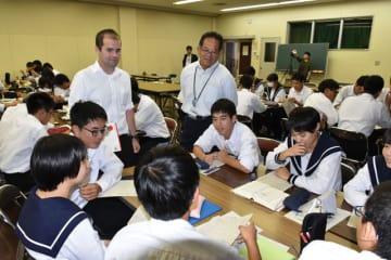 英語を使い、「在学中に海外留学しなければならない」というテーマで討論する生徒ら