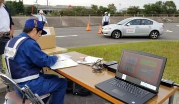 車検切れの模擬車両を走らせ、ナンバー自動読み取り装置の操作手順などを確認した研修会=22日午後、高松市