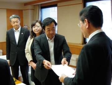 【前田議長(手前)に申入書を手渡す3会派の代表ら=県議会議事堂で】
