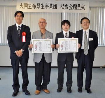 【贈呈状を受け取った矢野さん(右から2人目)、川村代表(同3人目)=津市栄町の大同生命三重支社津営業所で】