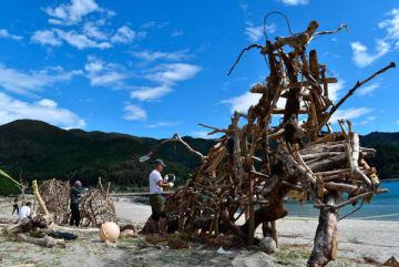 【流木で竜を制作する住民=尾鷲市三木里町の三木里海水浴場で】