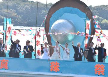 【船上から真珠玉を海に放つ関係者ら=志摩市阿児町神明の賢島港で】
