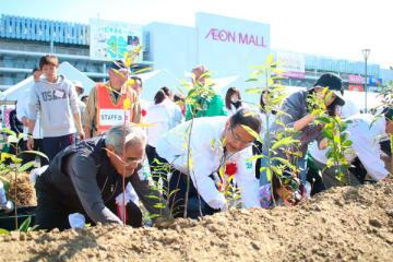 【苗木を植える岡田名誉会長(左)と前葉市長(左端から2人目)=津市高茶屋のイオンモール津南で】