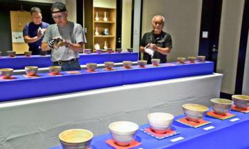 初出品となる「琉球緋文茶碗」を磨き開幕に備える関係者=22日、那覇市久茂地・タイムスギャラリー