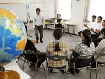 第三国定住制度で来日し、教室で職員(奥右)から日本語を学ぶミャンマー難民=2011年2月、東京都新宿区