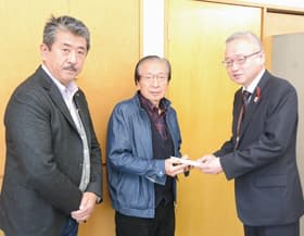 米野事務局長に益金を手渡す山川会長(中央)と山川社長(左)