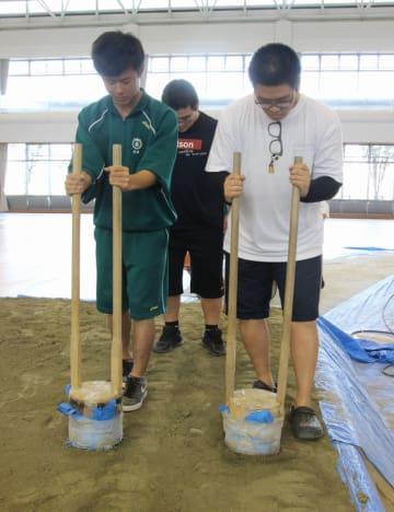 大相撲阿南場所を前に、道具を使って土俵を固める生徒たち=阿南市スポーツ総合センター