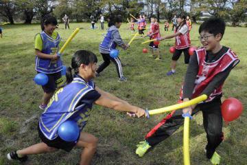 「エイッ」。チャンバラの要素も取り入れたスポーツ鬼ごっこを楽しむ子どもたち