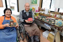 思い出の建物や家の写真を参考に、陶器を制作する木辻弘憲さん(右)。妻清子さんとともに働く=神戸市長田区海運町3、ピータンハウス
