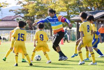 子どもたちと真剣勝負する九州レジェンズのノグチピント・エリキソンさん(中央)=福島県南相馬市の小高小学校グラウンド