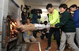 自らおこした火を石造りのまきストーブに移す児童=23日午前、六甲山小学校(撮影・辰巳直之)