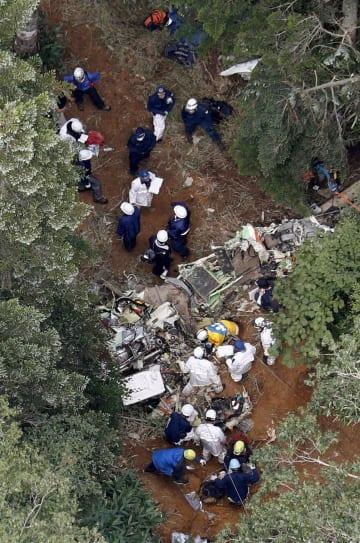 墜落した防災ヘリコプター「はるな」の残骸を調べる捜査員ら=8月11日、群馬県中之条町