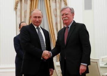 23日、モスクワで会談し、握手をするロシアのプーチン大統領(左)と米国のボルトン大統領補佐官(ロイター=共同)