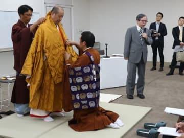 七条袈裟を重ねる僧侶の最高礼装の実演=京都市中京区・千總本社