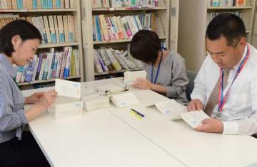 顕彰式の応募はがきの記載内容を確認する県の担当者