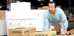 野菜を運ぶ木口さん。仕事が生きがいになっているという=秋田市公設地方卸売市場