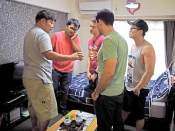 民泊に米国人4人組を迎え、部屋の使い方を説明する大藪さん(左端)=京都市北区