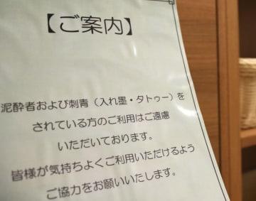 釜石市のホテル大浴場に掲げられた案内板。「入れ墨・タトゥーをされている方のご利用はご遠慮いただいております」と記載されている=11日