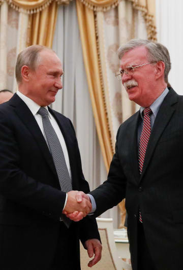 23日、モスクワで会談し握手するロシアのプーチン大統領(左)とボルトン米大統領補佐官(ロイター=共同)