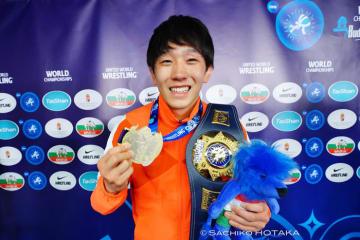チャンピオンベルトを肩にかけ、金メダルを見せる乙黒拓斗