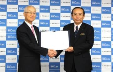 協定書を手に握手する鹿島理事長(左)と石渡理事長=神奈川歯科大