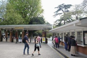 東京・新宿御苑の入場門と発券窓口(右)=24日