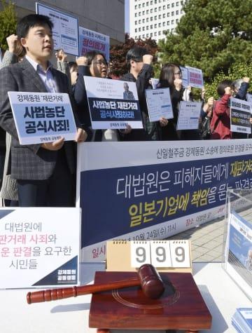 ソウルの最高裁前で開かれた集会に参加した市民ら=24日(共同)