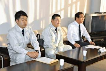 日米合意した新田原基地の米軍受け入れ施設整備の概要を新富町議会に説明する九州防衛局職員(左と中央)=24日午後