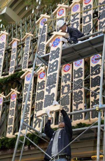 京都・南座の「まねき上げ」で、劇場正面に掲げられる歌舞伎役者の名前を書き入れた看板=25日午前、京都市