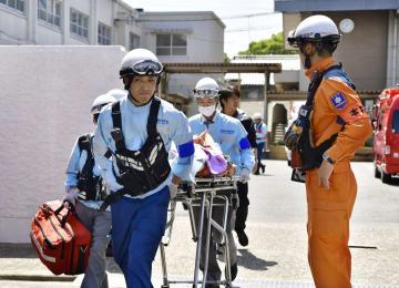 5月、熱中症とみられる症状で倒れた中学生を搬送する救急隊員=京都市