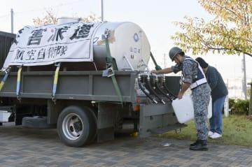 山口県大島防災センター前で給水支援をする自衛隊員=25日午後、山口県周防大島町