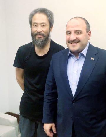 日本への帰国便に搭乗前、トルコのバランク産業技術相(右)と空港で面会する安田純平さん=24日、イスタンブール(アナトリア通信提供・共同)