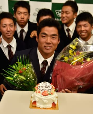 【指名祝福のケーキを前に笑顔を見せる菰野高校の田中法彦投手=菰野町福村の同校で】