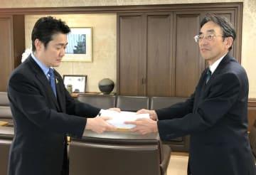 山下法相(左)に署名を手渡す「組織罰を実現する会」の松本邦夫副代表=26日午前、法務省(同会提供)