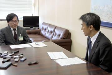 福井県の清水英男安全環境部長(左)に報告する日本原子力研究開発機構の伊藤肇理事=26日午前、福井県庁