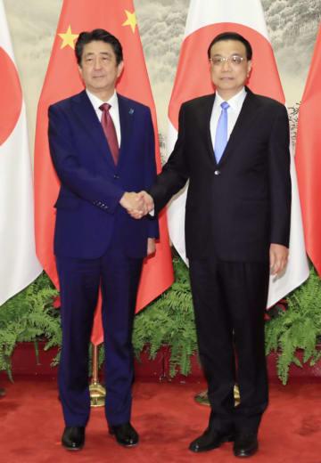 中国の李克強首相(右)と握手する安倍首相=26日、北京の人民大会堂(代表撮影・共同)