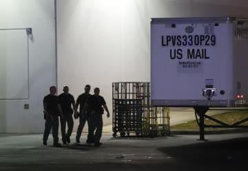 25日、不審な小包の発送元とみられる米フロリダ州の郵便施設を調べる捜査員(AP=共同)