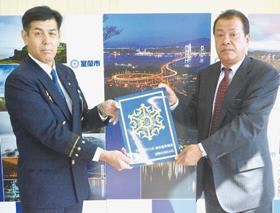 マークを受け取る及川隆社長(左)と佐藤徹也消防長