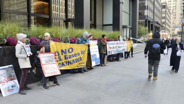 ニューヨークの日本総領事館前で、安倍政権の沖縄県への対抗措置に抗議する人たち=25日(共同)