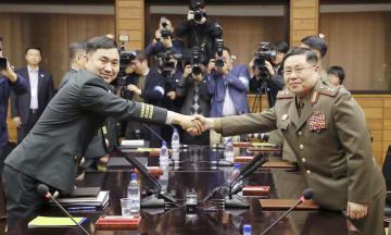 26日、板門店の北朝鮮側施設「統一閣」で会談後に握手する、韓国の金度均・国防省対北政策官(左)と北朝鮮の安益山・陸軍中将(韓国取材団・共同)