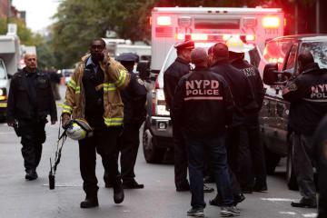 26日、米ニューヨークで不審な小包が見つかり対応する警官ら(ロイター=共同)